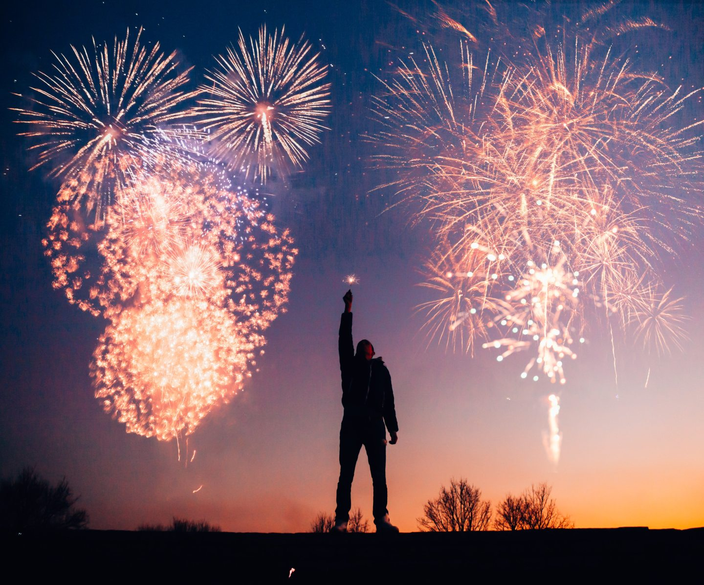 An image of a man holding a sparkler to a sky filled with fireworks