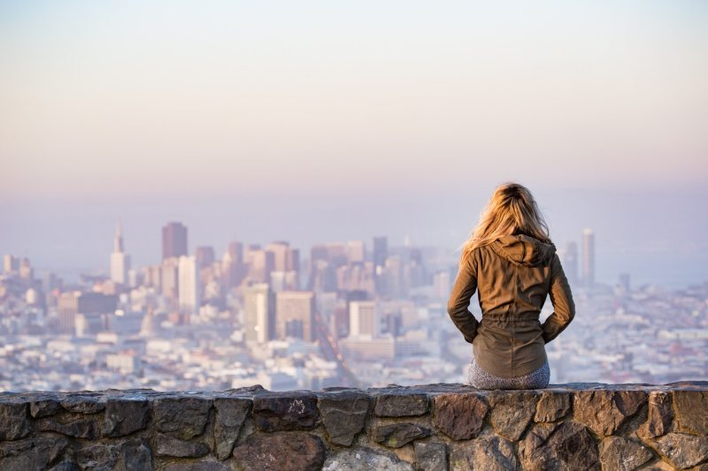 A picture of a woman sat looking over a San Fransisco skyline